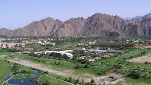 aerial of palm springs. roadside golf course with mountains in background. small pond, bunkers, trees on golf course. could be resort or country club. - palm springs california pool stock videos & royalty-free footage