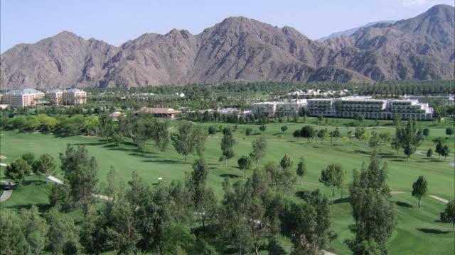 aerial of palm springs. golf course with mountains and hotels in background. pan down to man and woman on road riding bicycles. could be resort or country club. - palm springs california pool stock videos & royalty-free footage