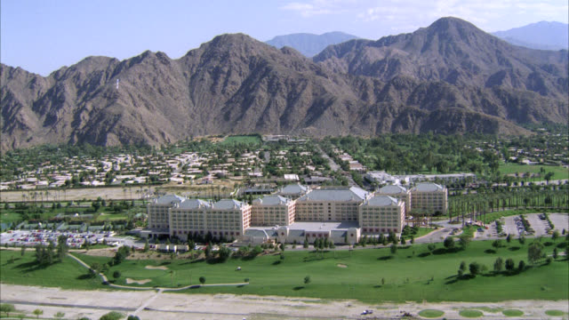 aerial of palm springs hotel and golf course. mountains in background. could be resort or country club. trees, grass, bunkers, blue skies. - palm springs california stock videos & royalty-free footage