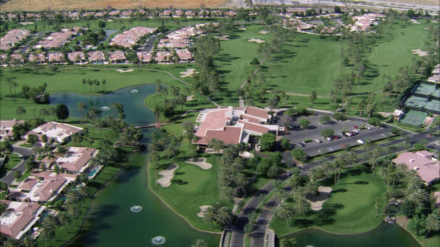 aerial of palm springs. golf course and small pond. middle class neighborhood houses, tennis courts, swimming pools, trees adjacent to golf course. - palm springs california pool stock videos & royalty-free footage