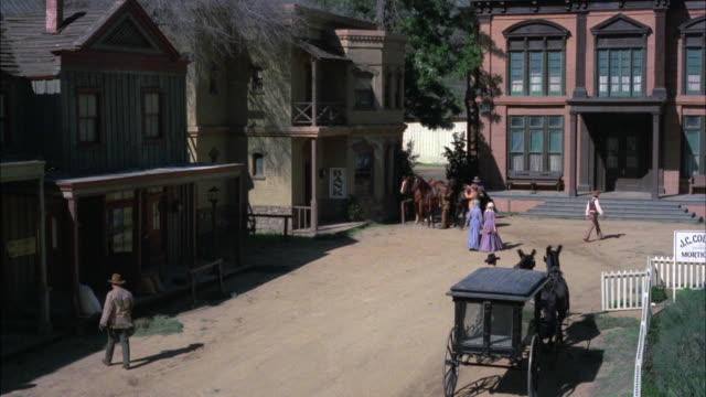 vídeos y material grabado en eventos de stock de high angle on western street. neg cut. western street in small town in old west. horses, cowboys, two story buildings, horse drawn carriage. match with 784-11. - oficio agrícola