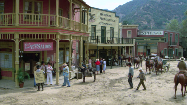 wide angle establish western saloon in small old west town horses. two story buildings. tourists walking. match 785-5 through 785-7. - wild west stock videos & royalty-free footage
