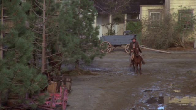 vidéos et rushes de pull back from establish shot of western town. wagon in bg, roads muddy from rain, cowboys horses. sign reads send pingree to congress. neg cuts. pine trees. - united states congress