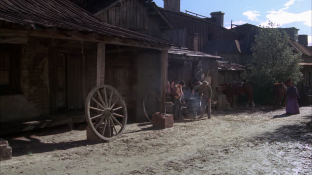 vidéos et rushes de wide angle establish western main street in small old west town. men carrying logs. wagon wheel. dirt road. cowboys. horse drawn wagon. neg cut. - animaux au travail
