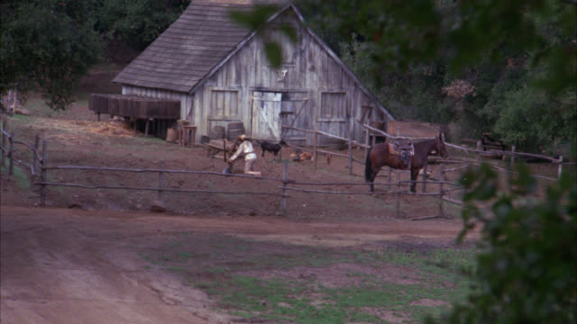 wide angle of barn with corral.man working on plow or other farm equipment. small animals in barnyard, could be goats and chickens.watch for principals  horse in bg. could be ranch. stables. - working animals stock videos & royalty-free footage