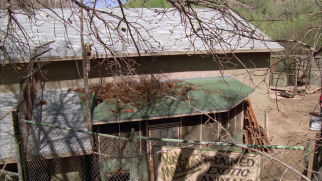 "wide angle est junkyard or run down barn or yard. sign in fg says ""rick macklan's trained exotic animals"". static shot. house, roof, fence. - 1987 stock videos & royalty-free footage"