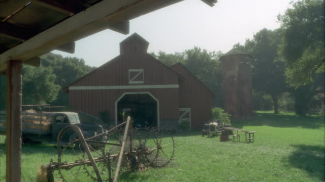 vidéos et rushes de est medium close shot of  red barn stable with silo next to it in green countryside setting. see pick up truck and farming equipment parked. grain, corn storage. tractor, farm equipment. - ferme bâtiment agricole