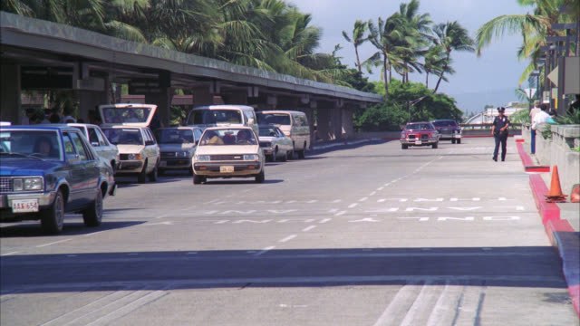 vídeos y material grabado en eventos de stock de wide angle , pan right to left on limousine as it pulls away from honolulu airport terminal. runby. palm trees, cars, trucks, vans, traffic, airport activity. passengers. - honolulu