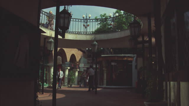 wide angle of an outdoor shopping mall. atrium. no roof. brick tiled area. pedestrians, shoppers walking strolling, milling about. - shopping centre stock videos & royalty-free footage
