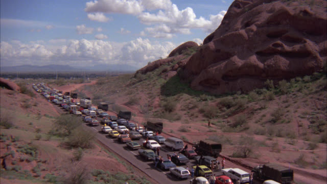 HIGH ANGLE DOWN OF FOUR LANE ROAD OR HIGHWAY IN THE DESERT HILLS. CARS ON THE ROAD ARE STOPPED. TRAFFIC JAM. PEOPLE WALKING ON THE ROAD. MILITARY CARAVAN OR CONVOY WITH JEEPS, COVERED PERSONNEL CARRIERS AND AMBULANCES. VEHICLES. COULD BE EVACUATION.