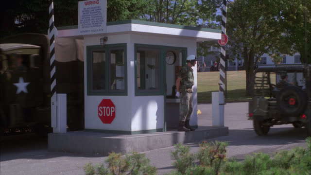 """pan down to army post or base security checkpoint. people or soldiers in uniform. army jeeps and trucks going through gate. guard shack. sign in bg reads """"camp murray  washington national guard"""". - 掘建て小屋点の映像素材/bロール"""