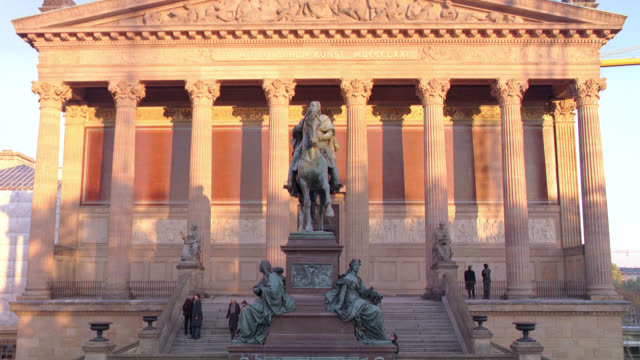 "pan up from entrance to the old national gallery. ""der deutschen kunst"" or art museum. stone building with classical pillars or columns. staircases. bronze statues including one of frederick william iv on a horse. - kunst stock videos & royalty-free footage"