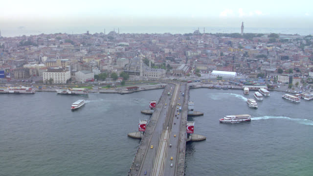 aerial tracking black suv and car or sedan over the galata bridge over the golden horn harbor and onto city streets. strait of bosphorus. european or near eastern city. multi-story apartment or office buildings. ferry boats in water. - istanbul stock videos & royalty-free footage