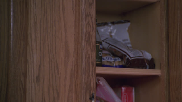 close angle of wooden kitchen cabinet with food inside. raisin bran cereal, canned peas, quaker puffed wheat. - cupboard stock videos & royalty-free footage