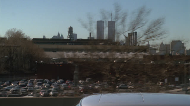 vídeos de stock e filmes b-roll de tracking shot of  1974 mercedes-benz s-klasse car driving on freeway or highway. cars and trucks follow. world trade center or twin towers visible in bg. - world trade center manhattan