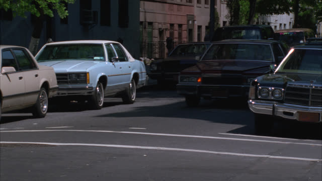wide angle of 1979 cadillac coupe deville driving turing street corner on nyc street. trucks and other cars drive on street. pedestrians. - キャデラック点の映像素材/bロール