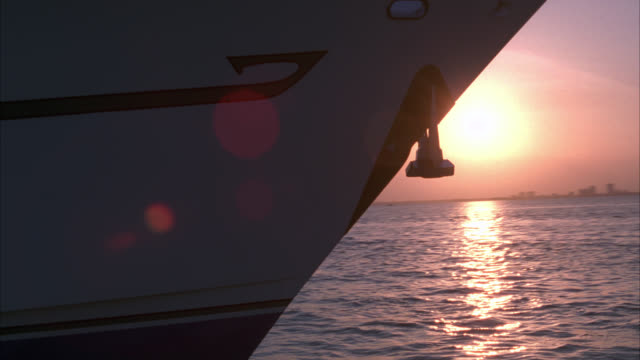 pan left to right across front or bow of yacht or boat in bay, ocean or harbor. upper class. sunset and sun halation in bg. - stereotypically upper class stock videos & royalty-free footage