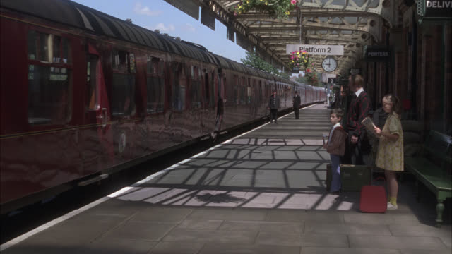 tracking shot of passenger train leaving train station. people or passengers waiting on platform. could be in small town. - railway station stock videos & royalty-free footage