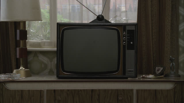 close angle of television with antenna on top, on table in front of window. wood paneling on walls. burn-in. - living room stock videos & royalty-free footage