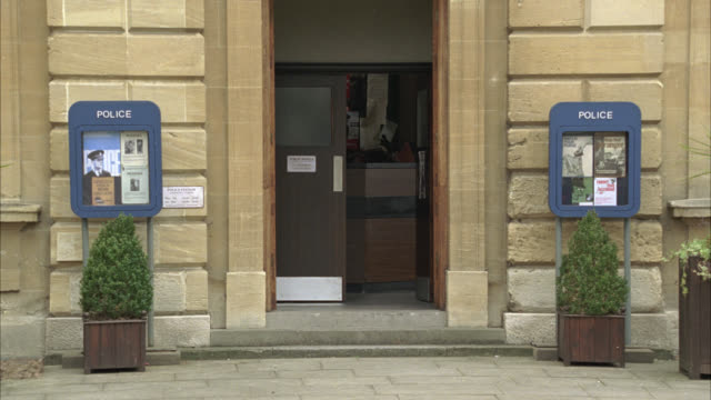 medium angle of entrance to stone building or police station in small english town. - police station stock videos & royalty-free footage