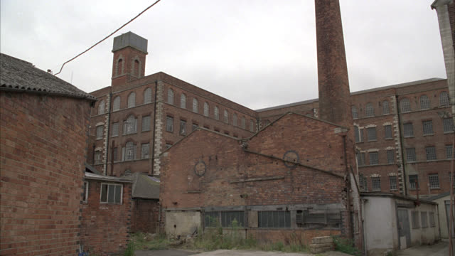 zoom in from wide angle of brick factory or warehouse. smokestack visible in fg. abandoned or rundown industrial area and building. camera zooms in to warehouse window. overcast sky. - warehouse stock videos & royalty-free footage