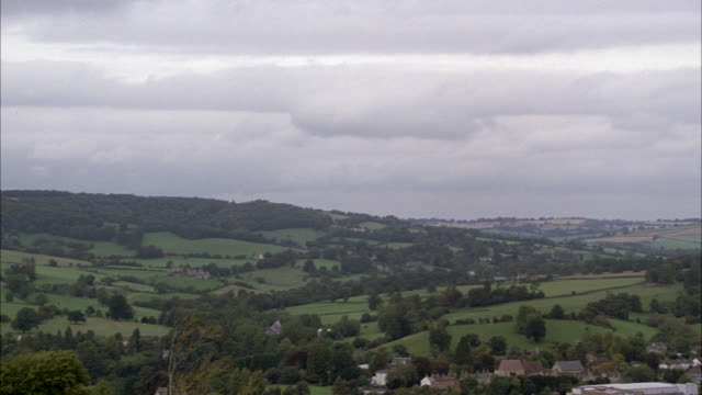 pan down right to left from overcast sky to english village or town in countryside. rural area or country. trees, rolling hills, and fields. - field stock videos & royalty-free footage