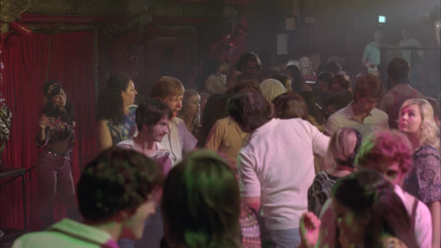 vidéos et rushes de medium angle of people dancing. could be night club. crowds. people wear 1970s attire. could be hippies. disco clubs. - 1970