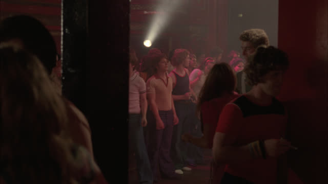medium angle of people dancing. could be night club. crowds. people wear 1970s attire. could be hippies. disco clubs. could be theater. - anno 1970 video stock e b–roll