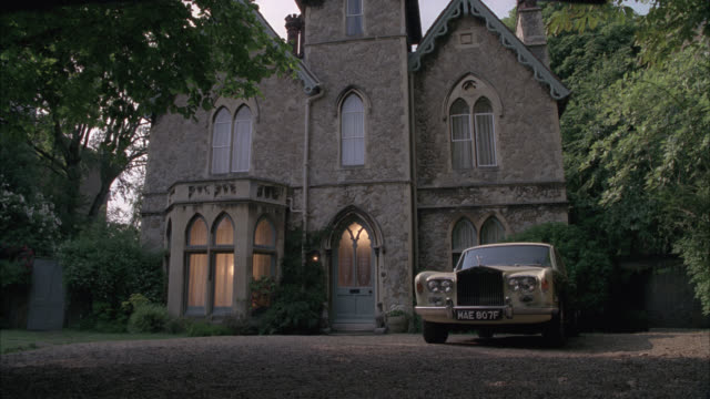 wide angle of 1967 jaguar 420 luxury car parked in driveway of english manor or mansion. upper class house. could be estate. gothic style. - stereotypically upper class stock videos & royalty-free footage
