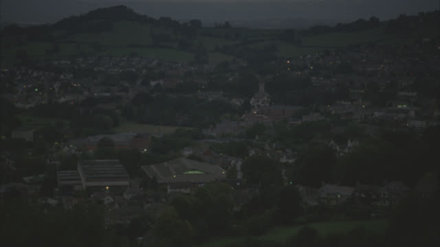 wide angle of town or village in english countryside. lights visible in town. valley. hills and fields visible in bg. trees. - 2010 stock videos & royalty-free footage