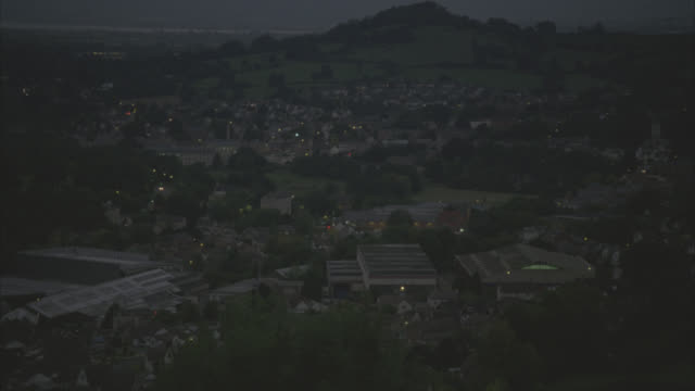 pan left to right of town or village in english countryside. lights visible in town. valley. hills and fields visible in bg. trees. - 2010 stock videos & royalty-free footage