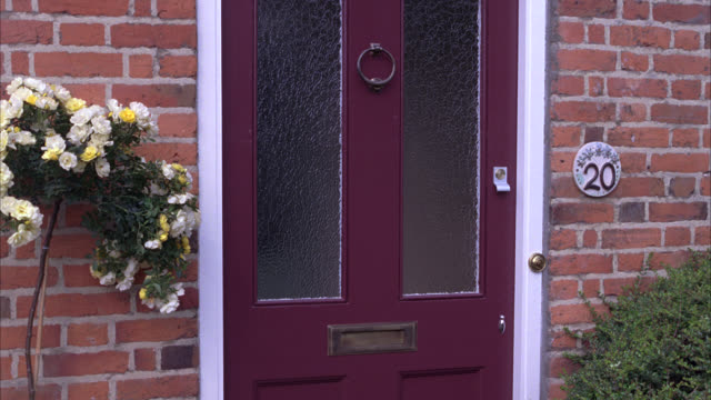 medium angle of front door or entrance to brick house. number 20 on sign, address. flowers, bushes, shrubs. middle class. - 2010 stock videos & royalty-free footage