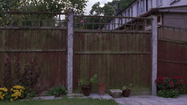 vidéos et rushes de pan left to right of wooden fence in backyard. potted plants and flowers. lower to middle class suburban neighborhood. - clôture jardin