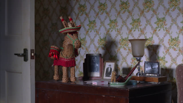 zoom in on figurine of donkey made of straw, wearing sombrero or hat, on top of bureau or dresser. photos, clock and pipe. bedroom. donkey moves on its own. - figurine stock videos and b-roll footage
