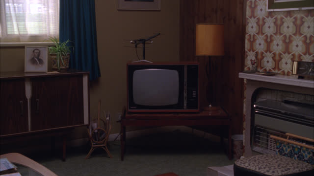 medium angle of television in corner of living room. wood panels on wall. photo of man under window. burn-in. - living room stock videos & royalty-free footage