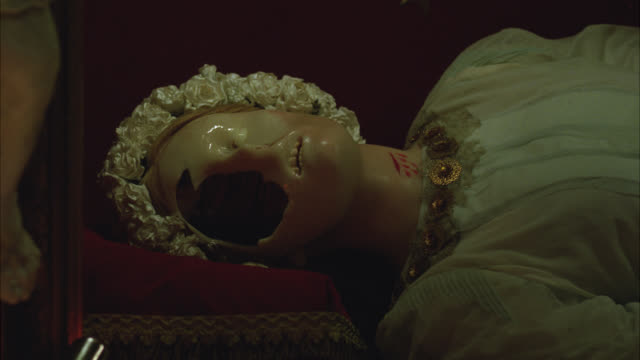 close angle of face of wax statue melting. religious figure on display in church. figure has crown of roses or flowers. ornate. christianity and catholicism. - scultura video stock e b–roll