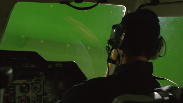 close angle of man, pilot flying helicopter. cockpit with instrument and control panels. green screen. - helicopter stock videos & royalty-free footage