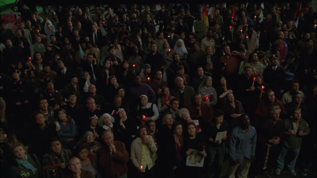 vidéos et rushes de high angle down of crowd of people in large plaza looking up at sky. people holding candlelight vigil, praying. catholic church. - bougie