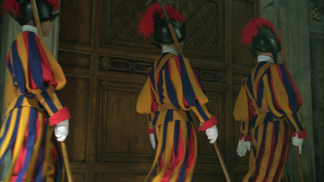 medium angle of swiss guard in stripped uniforms marching in front of door in vatican city. walk past door with lock. could be conclave guards. security guards. men wear helmets with plume or feather and carry axes. - 2009 stock videos & royalty-free footage
