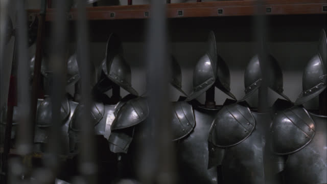 pan right to left across row of axes or bayonets in fg to suits of armor in bg. spanish style. multiple takes. could be armory. - 武器庫点の映像素材/bロール