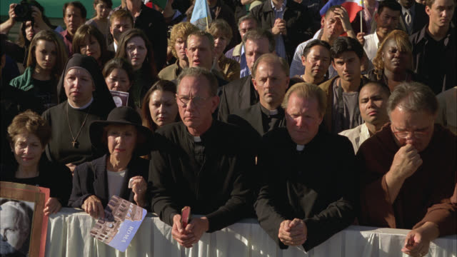 medium angle of crowd or tourists standing mournfully behind barrier. swiss guard or vatican city guard watches fence. nuns and priests among crowd. religious event. people crying and sorrowful. catholic. green screen in bg. - state of the vatican city stock videos & royalty-free footage