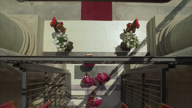 high angle down over doorway as funeral procession of pope passes underneath. cardinals and priests walk out with deceased pope's body on platform. dead bodies. flowers adorn pillars or columns at entrance of doorway. swiss guard visible. religious ceremo - prete video stock e b–roll