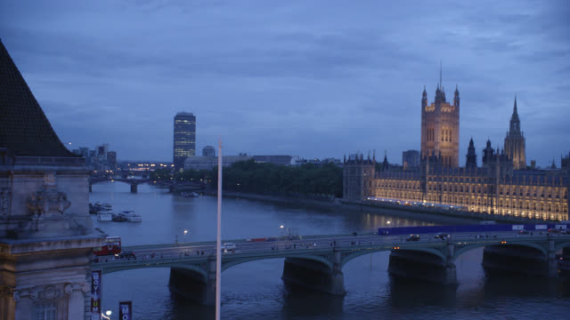 high angle down of westminster bridge spanning thames river in london. parliament buildings in bg. government buildings. cloudy. people walk across bridge. cars driving. water. lights. movieum or london film museum in fg. landmarks. - 2009 stock videos & royalty-free footage