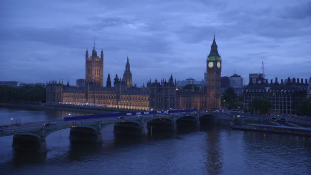 high angle down of westminster bridge spanning thames river in london. parliament buildings and big ben clock tower in bg. government buildings. cloudy. people walk across bridge. cars driving. water. lights. landmarks. - 2009 stock videos & royalty-free footage