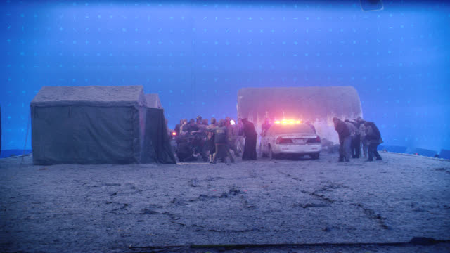 medium angle of people at refugee camp during earthquake. emergency. tents. lights flashing on bizbar of police car. military or army soldiers. blue screen. natural disaster. - barracks stock videos & royalty-free footage