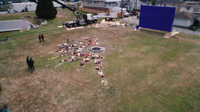 vídeos y material grabado en eventos de stock de high angle down of people lying on grass in semi-circle around fire pit. could be mass-suicide, religious or cult ritual. field or meadow. could be dead bodies or corpses. blue screen. police officers, crime scene investigators, photographers. - ceremonia