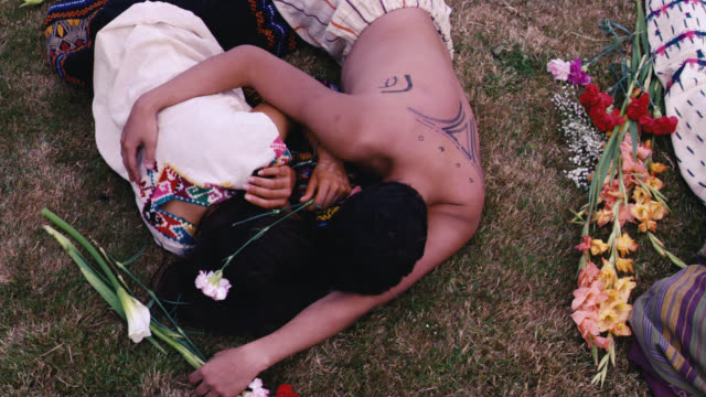 pan up of people lying on grass in semi-circle around smoking fire pit. could be mass-suicide, religious or cult ritual. field or meadow. could be dead bodies or corpses. men, women, children. flowers. could be villagers or natives. police officers, crime - crime stock videos and b-roll footage