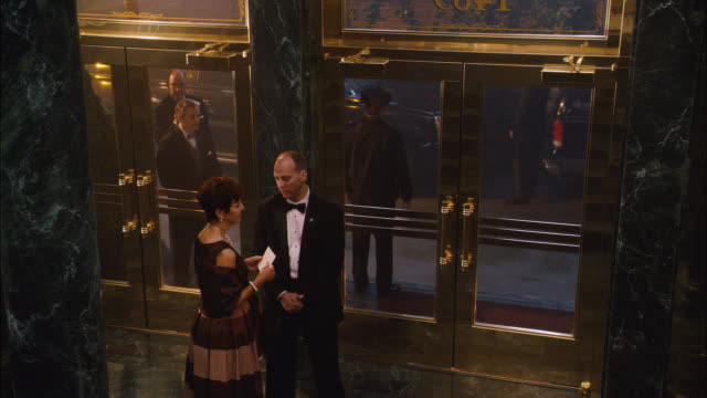 high angle down of people standing at entrance to upper class hotel or lobby. could be for gala event, reception, fundraiser, wedding or party. black tie. - stereotypically upper class stock videos & royalty-free footage