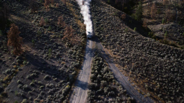 aerial of rv driving down dirt road. dry, arid landscape and shrubs. could be rural area. - camper van stock videos & royalty-free footage