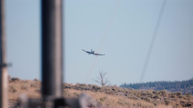 pan right to left of small private propeller plane shakily flying over pine trees in woods or forest. mountains. - propeller video stock e b–roll